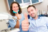 Portrait of a young attractive dentist in his office with patien