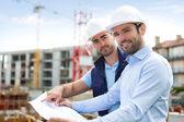mérnök és figyeli a blueprint építkezésen dolgozó