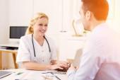 Mladý atraktivní lékař poslouchá svého pacienta