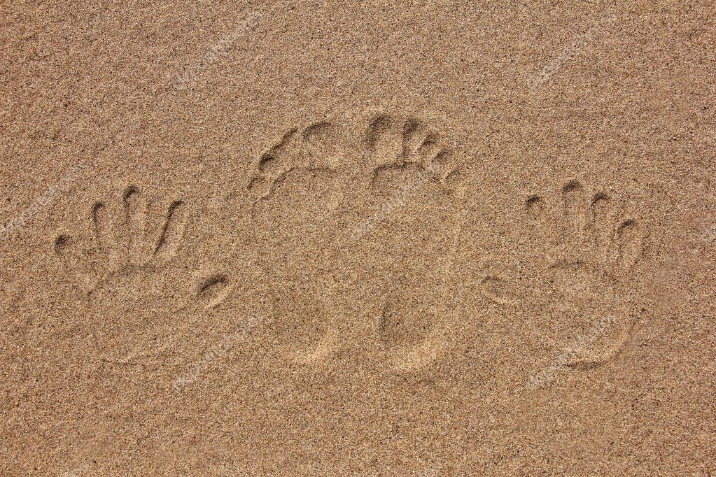imprint of feet and hand on the sand