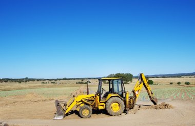 Yellow excavator on agriculture field