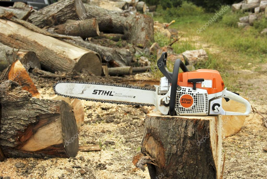 Stihl chainsaw on a log outdoors stock editorial photo stihl chainsaw on a log outdoors stock photo keyboard keysfo Image collections