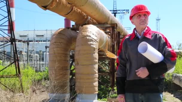 Pracovník v červená čepice s konstrukční výkresy na teplárny