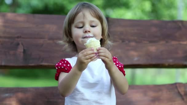 Little girl sits on the bench and eats ice cream