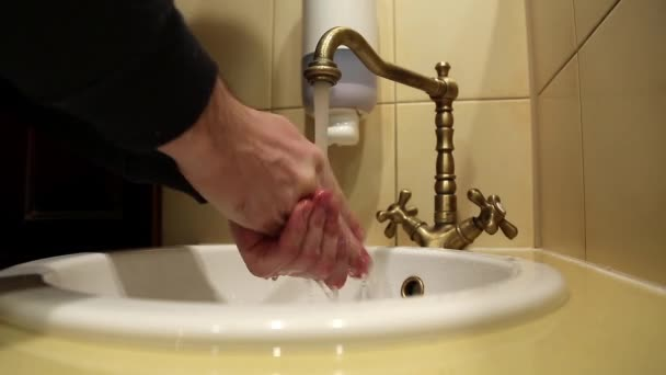 Man washes his hands in sink