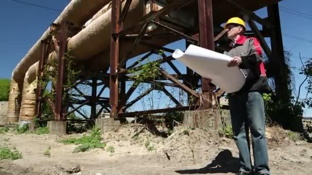 Dělník v přilbu s výkresy projektu