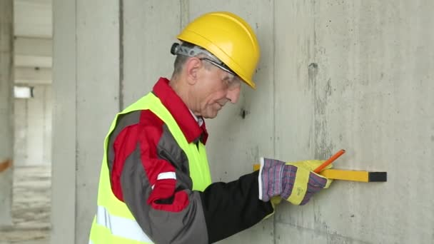 Worker in yellow hard hat with level