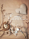 Ostereier, Zweig mit Knospen und weißem kalligraphischen Wort Ostern auf Kraftpapier.