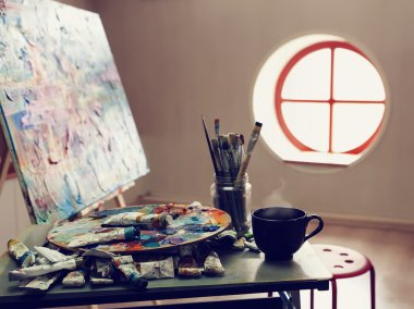 Paintbrushes, artist palette, pencils, coffee cup, watercolor and oil paints on desk in painter studio. stock vector