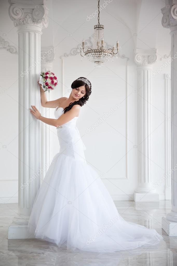 Schöne Brünette Braut in einem Brautkleid und einer Krone auf ihrem ...