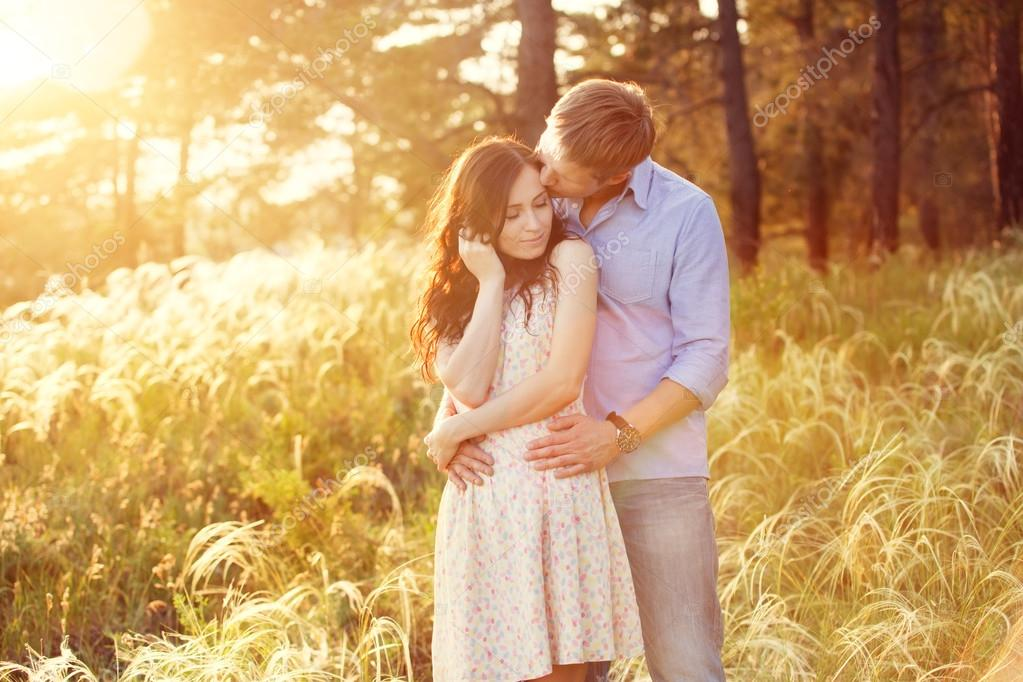 young couple in love at sunset in the field