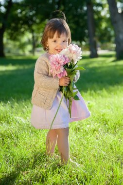 Sweet toddler girl with flowers bunch in hands
