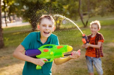 boys having fun playing with water guns