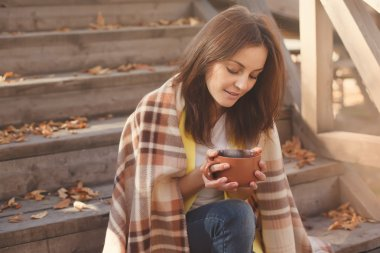 Young woman resting and drinking tea sitting in autumn garden on the steps, wrapped in a woolen plaid blanket.