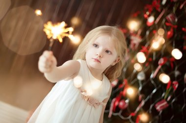 little girl holding firewors  on Christmas tree background