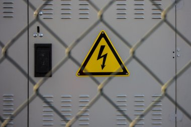 electrical hazard sign placed on a electric power substation behind a metal fence of wire mesh