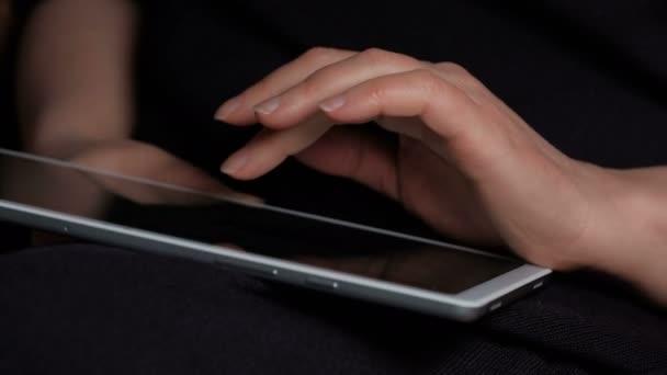 Egy nő keze, aki egy fekete hátterű tableten nézi a híreket.