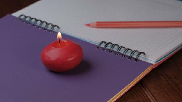 Kis piros kerek gyertya ég mellett egy notebook közeli 4k videó