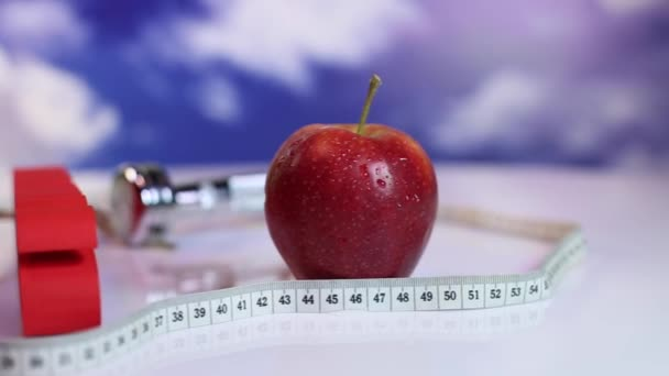 Measuring tape around apple with dumbbell