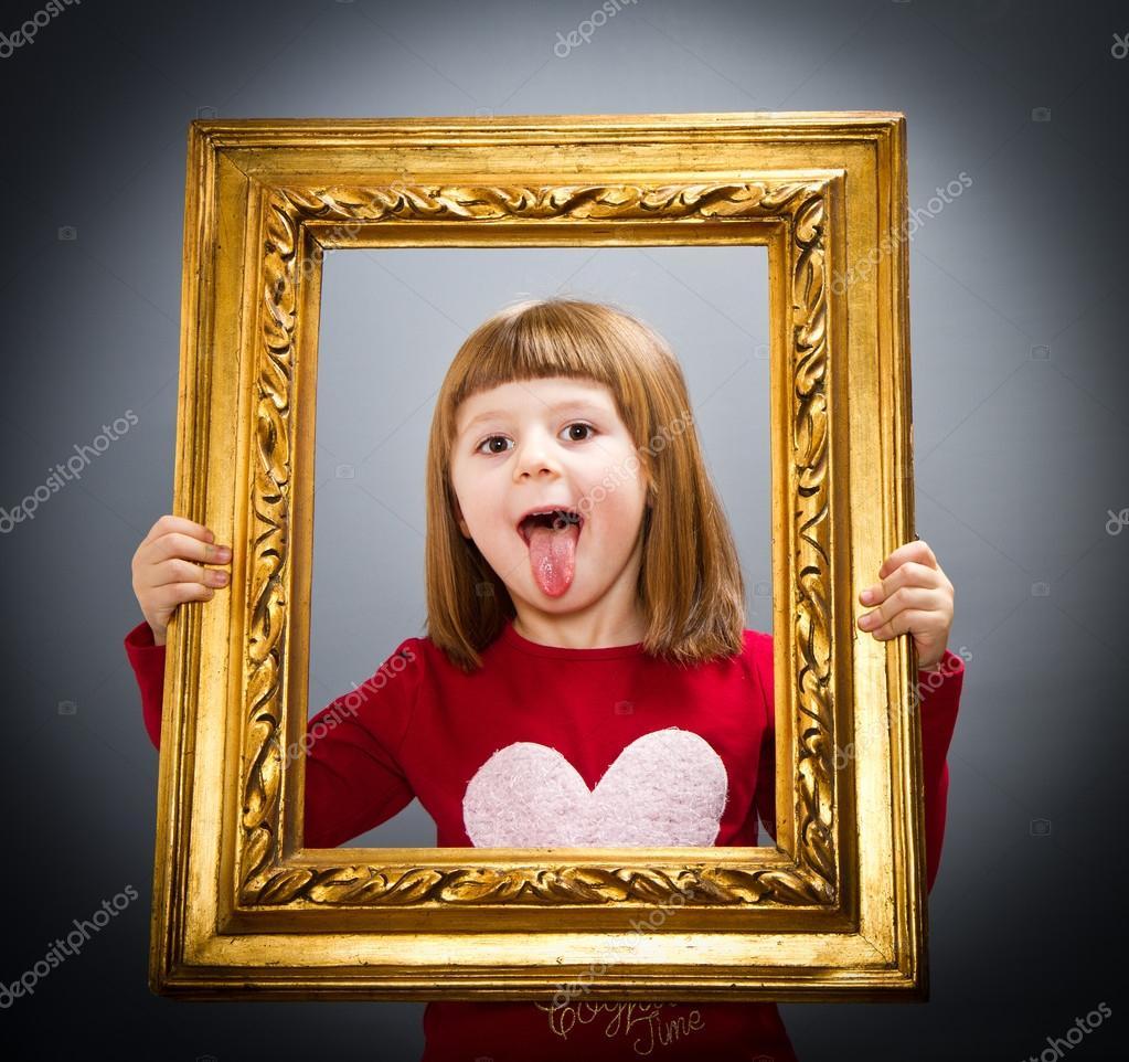 niña sonriente mirando a través de un marco de imagen vintage — Foto ...