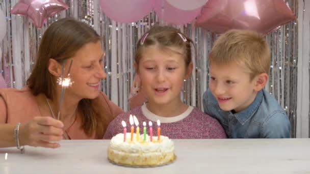 Šťastná holčička slaví narozeniny s rodinou, která sfoukne svíčky na dortu. její rodina sleduje malé dítě sfouknutí dort svíčky.