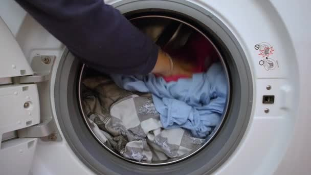 Előkészítem a mosási ciklust. Mosógép, kéz és ruha