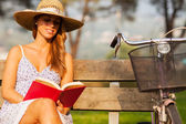 brunette woman sitting on a bench with a book in her hands