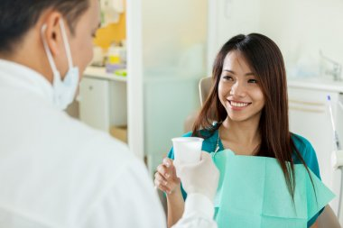 Asian woman is taking a glass of water from her dentist