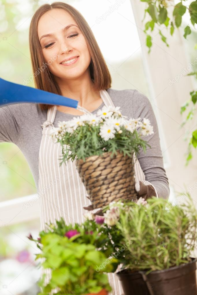Smiling woman is pouring water in the plants