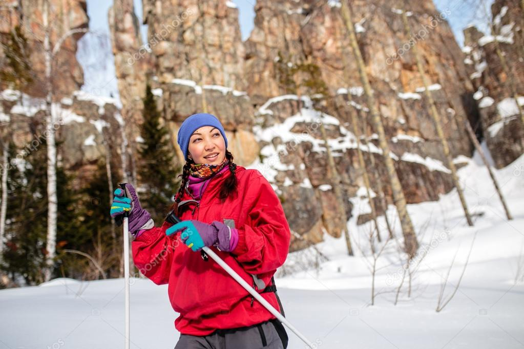 Girl tourist in winter on a background of red rocks, Ural mounta