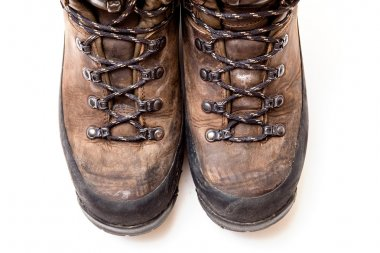 Old scuffed hiking boots isolated on white background