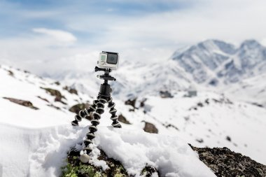 Action camera mounted on a tripod gorilla with snow-capped mount