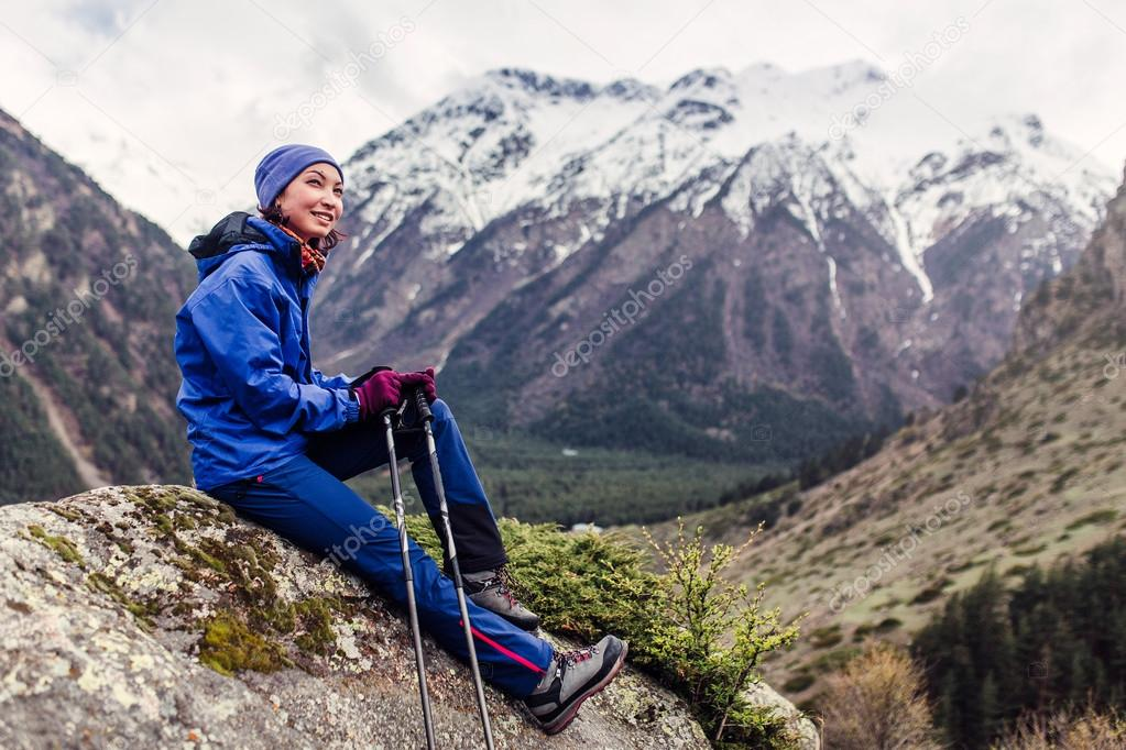 Woman hiker relaxing and resting on the rock at top of the mountain, Caucasus