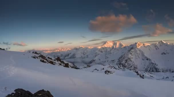 Timelapse sunset in snowy mountain ridge with glacier and red clouds