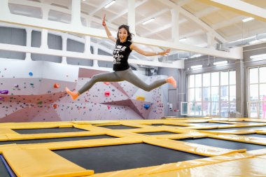 Jumping young and funny woman on a trampoline in fitness centre