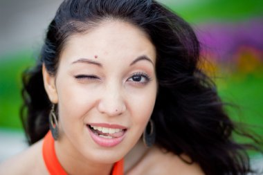 Young happy brunette woman winking