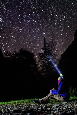 Woman looking at stars with headlamp gleaming