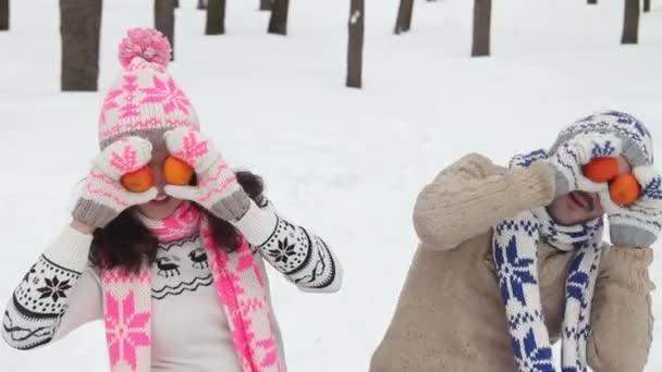 Liebespaar im Winterpark mit Spaß und Spiel. der Mann und die Frau legen eine Mandarine vor ihre Augen und lachen