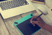 designer with laptop and graphics tablet
