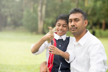 indian father and son playing slingshot