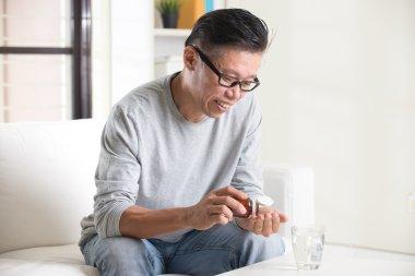 asian senior male taking pills