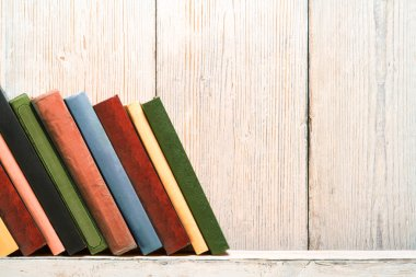 Books Wood Shelf, Old Spines Covers on White Vintage Wooden Wall