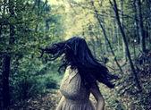 Ijedt nő fut keresztül erdő