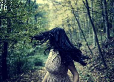 Scared woman running through forest