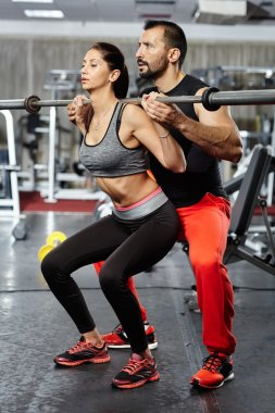Doing squats with barbell helped by personal instructor