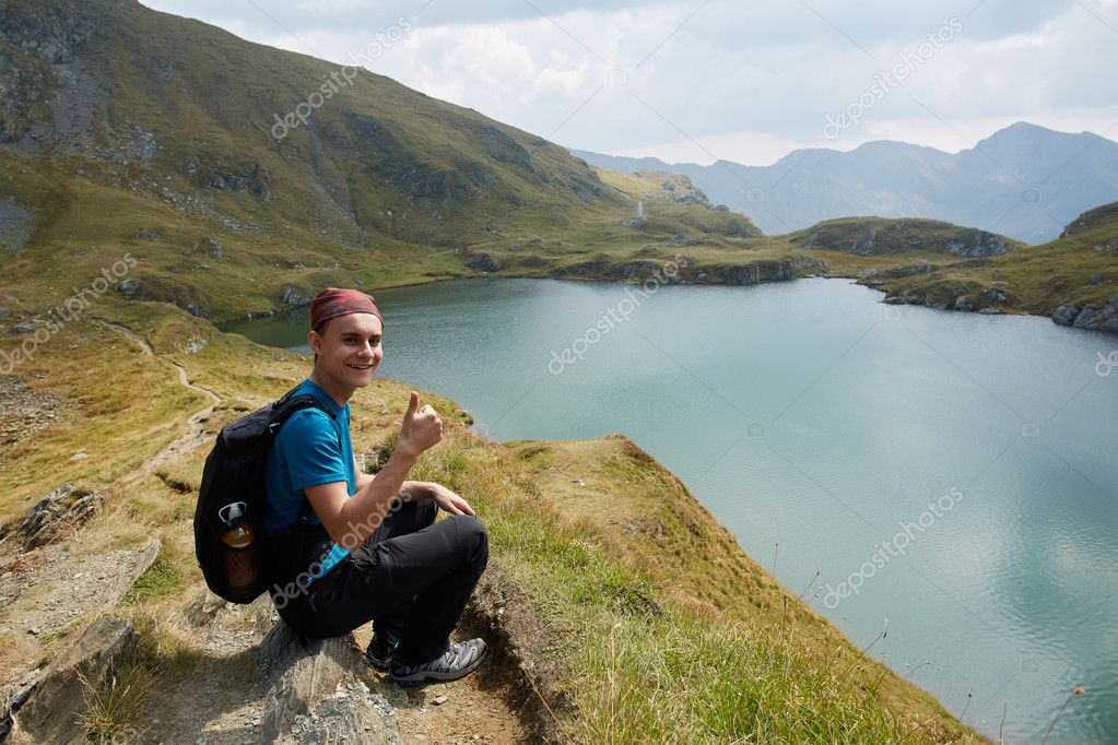 Hiker boy with backpack by the lake