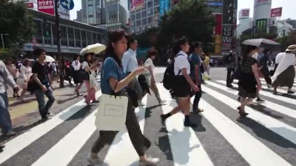 people cross the Shibuya intersection in Tokyo