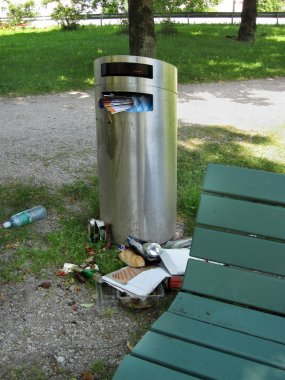 Over full trash can in city park