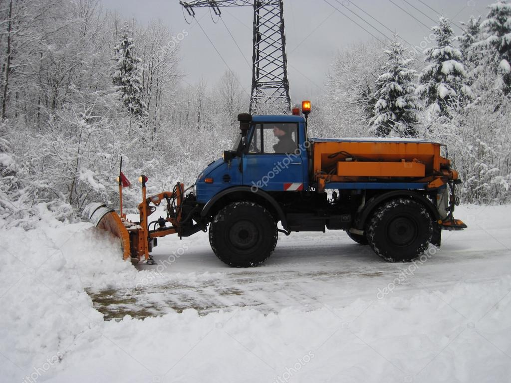 Machinery with snowplough cleaning road by removing snow from in