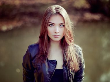 Portrait of young beautiful woman in leather jacket